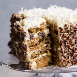layered carrot cake with buttermilk cream cheese frosting on a glass cake stand with gray background