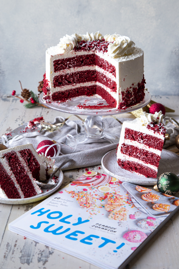Sliced red velvet peppermint cake with Holy Sweet! cookbook in foreground